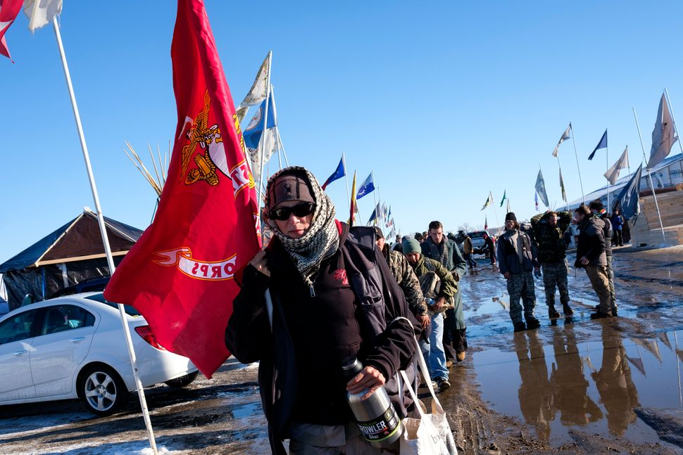 Lita Boyd, a veteran of the U.S. Army, leads a group of veterans to the checkin area at the Oceti Sakowin campground north of