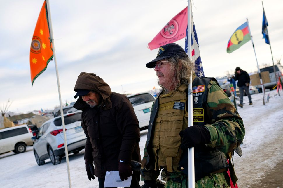 Rob McHabey, right, a U.S. Navy veteran, walks with Ben Wright, left, a U.S. Army Veteran, at the Oceti Sakowin campground.