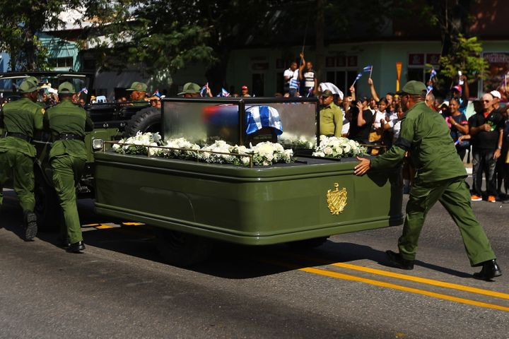 Soldiers push the vehicle and trailer carrying the ashes of Fidel Castro after it broke down during the procession.