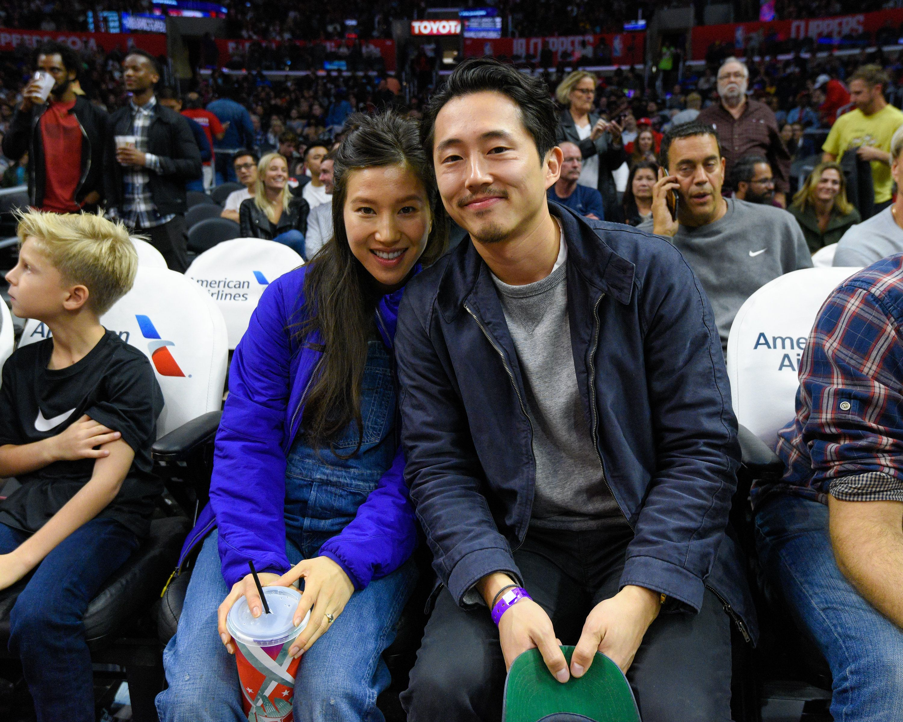 LOS ANGELES, CA - NOVEMBER 07:  Steven Yeun (R) and Joana Pak attend a basketball game between the Detroit Pistons and the Los Angeles Clippers at Staples Center on November 7, 2016 in Los Angeles, California.  (Photo by Noel Vasquez/GC Images)
