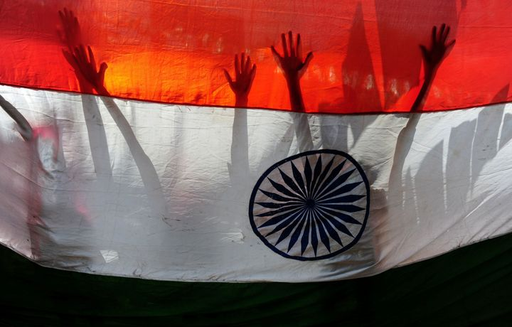 Indian schoolchildren stand behind a national flag during Independence Day celebrations in Chennai on Aug. 15.