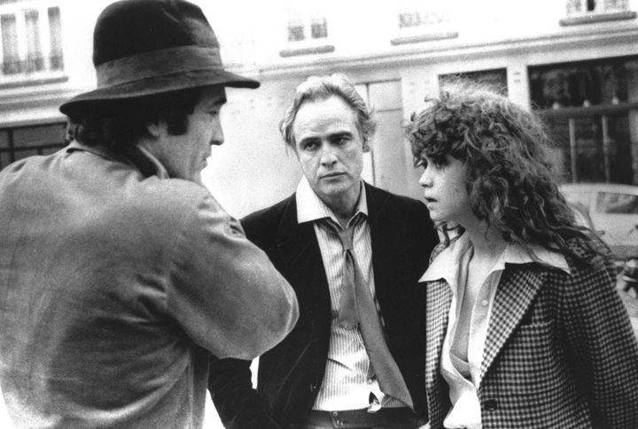 "Bernardo Bertolucci, left, discusses a scene from ""Last Tango in Paris"" with Marlon Brando and Maria Schneider."
