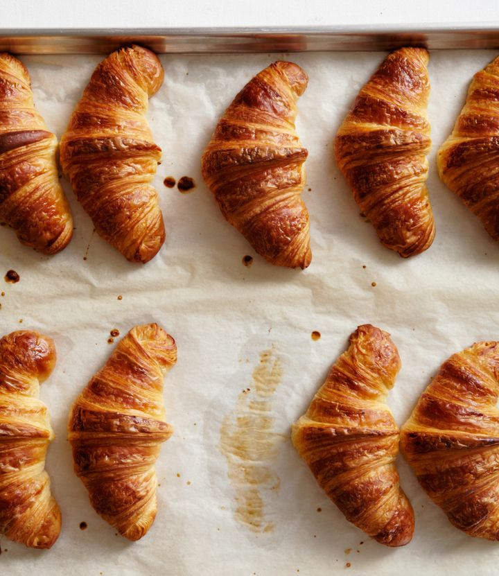 A line of croissants on a baking tray.