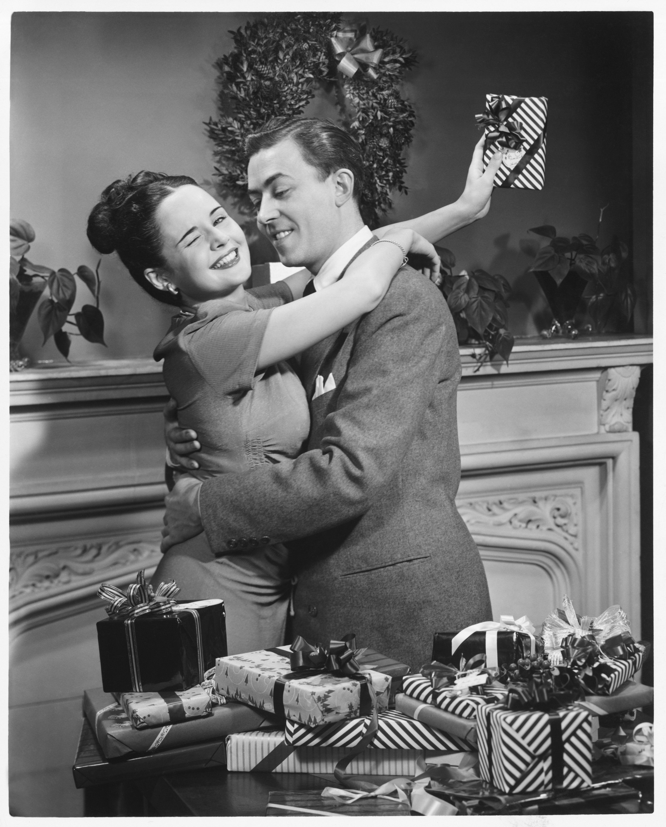 Couple embracing at table with Christmas presents, (B&W)