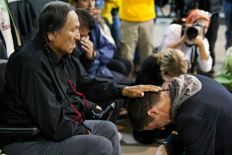 Leonard Crow Dog, a Lakota elder and highly-regarded activist, left, places his hand over Wesley Clark Jr.'s head during a fo