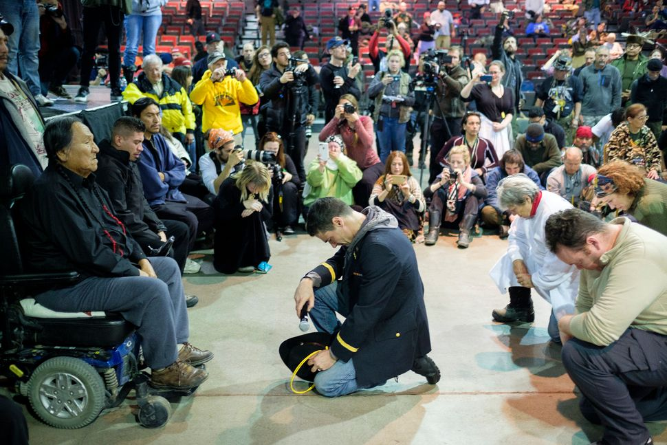 Wesley Clark Jr., middle, and other veterans kneel in front of Leonard Crow Dog during the forgiveness ceremony.