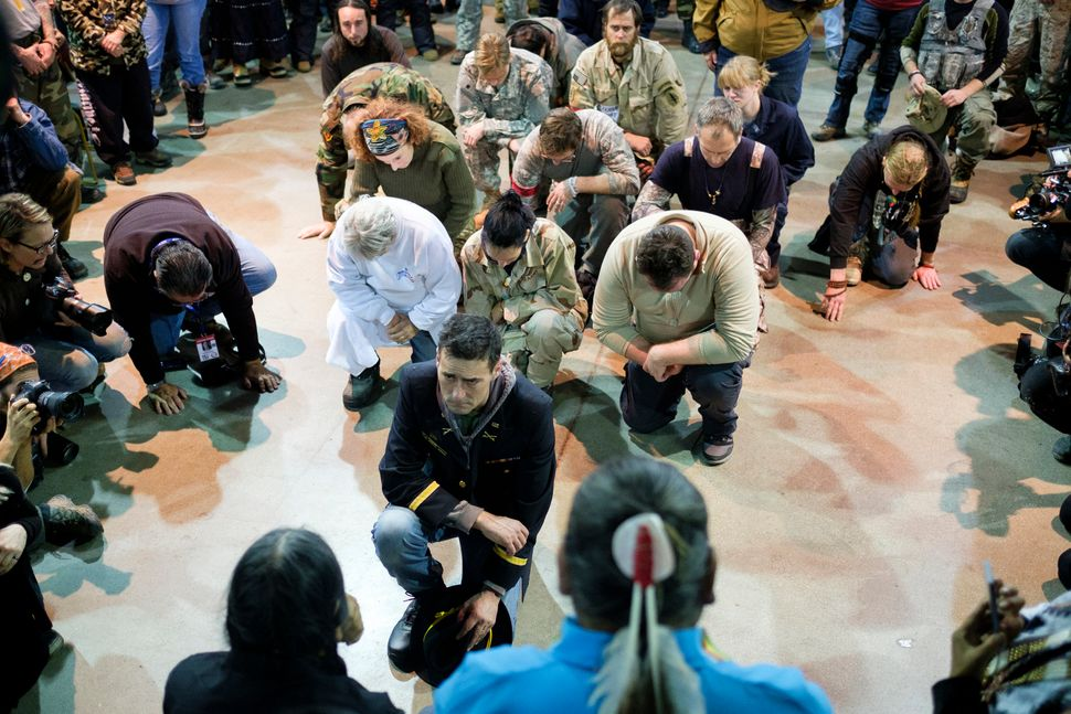 Wesley Clark Jr. and other veterans kneel in front of Leonard Crow Dog during a forgiveness ceremony at the Four Prairie Knig