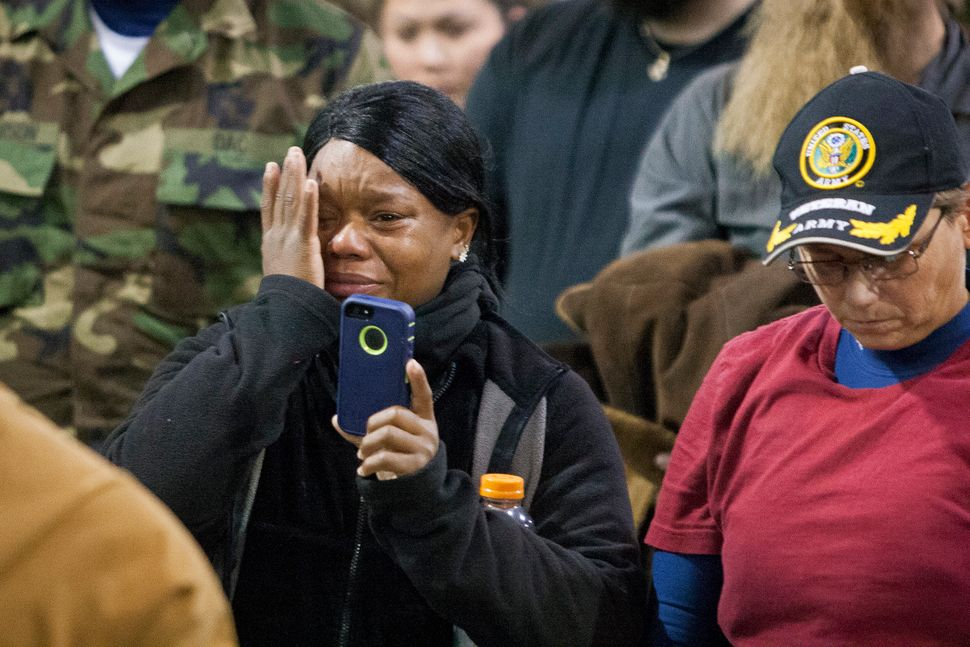 Veteran Tatiana McLee wipes tears from her eyes as she films Lakota elders speak during the forgiveness ceremony.