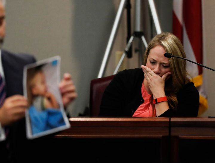 Leanna Taylor is seen crying on the stand as an attorney holds up photos of her son, Cooper, who died after being left inside