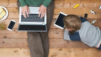 top view of mother and son using digital media. Modern online generation addicted to internet.