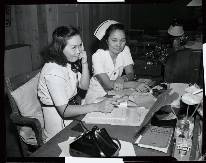 A newspaper photo shows two Japanese-American workers at an emergency medical unit in Honolulu, with the caption saying they