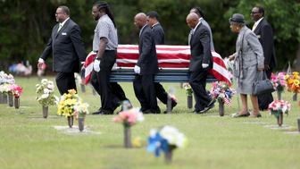 CHARLESTON, SC - APRIL 11: The flag drapped coffin of Walter Scott is carried by pallbearers to his burial site at the Live Oak Memorial gardens cemetery, after he was fatally shot by a North Charleston police officer after fleeing a traffic stop in North Charleston on April 11, 2015  Charleston, South Carolina. Mr. Scott was killed on April 4 by North Charleston police officer Michael T. Slager after a traffic stop. The officer now faces murder charges. (Photo by Joe Raedle/Getty Images)