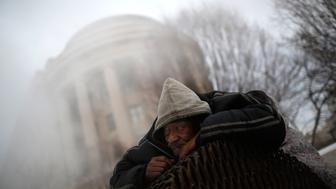 WASHINGTON, DC - FEBRUARY 17:  Donnie Prince, who is homeless, tries to stay warm on top of a steam grate outside the Federal Trade Commission on Constitution Avenue February 17, 2015 in Washington, DC. The Washington DC area received 4-6 inches of snow overnight as a winter storm hit large areas of the east coast. (Photo by Win McNamee/Getty Images)