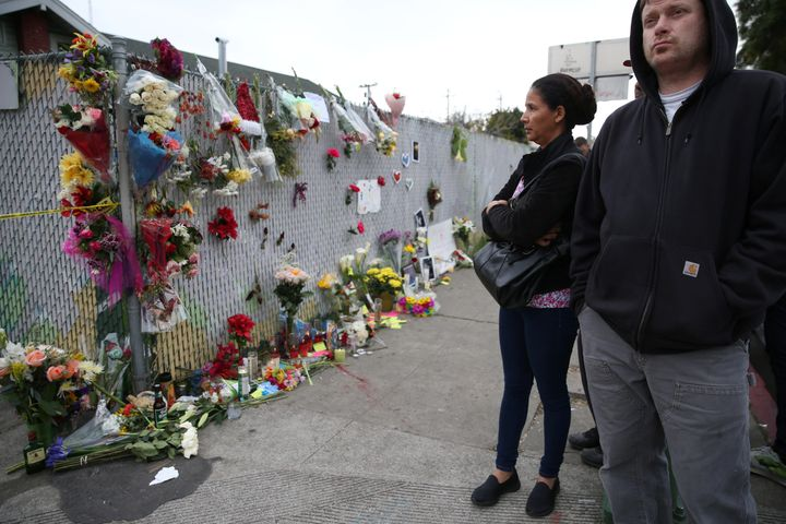 People view a sidewalk memorial near the burned Oakland warehouse on Dec. 5, 2016.