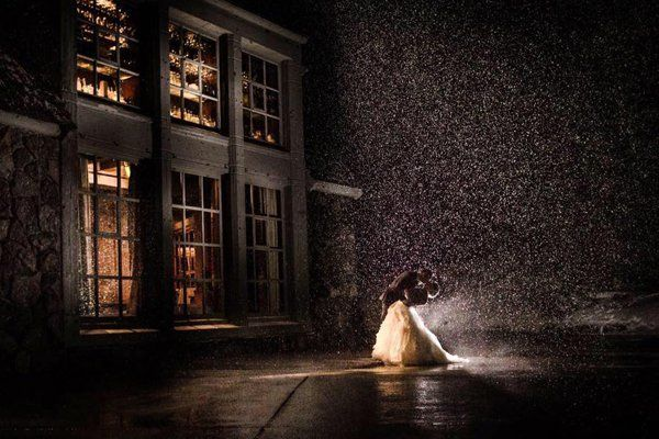 The night sky and a street lamp combine to shine a spotlight of dramatic snowfall on this couple, making for a magical shot.