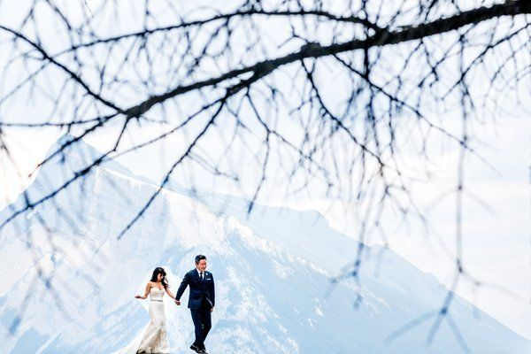 A delicate bare branch frames the newlyweds and the mountain behind them, making for a creative angle in a postcard-worthy sh