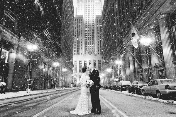 A black and white still of a city getting sprinkled in snow as bride and groom share a kiss is nothing but glamorous.