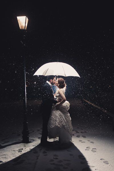 An umbrella not only shields this cute couple from the snow, but it acts as the perfect frame for their love.