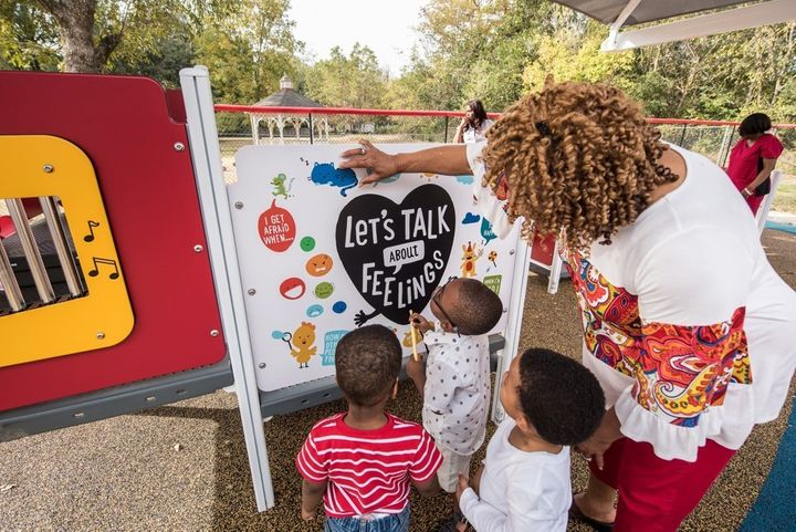 <p>Young children examine a literacy panel similar to the ones at Officer Willie Wilkins Park in Oakland, California.</p>