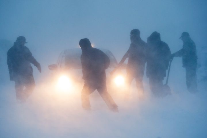 Several people attempt to free a vehicle from the snow in the Prairie Knights Casino and Resort parking lot during a blizzard