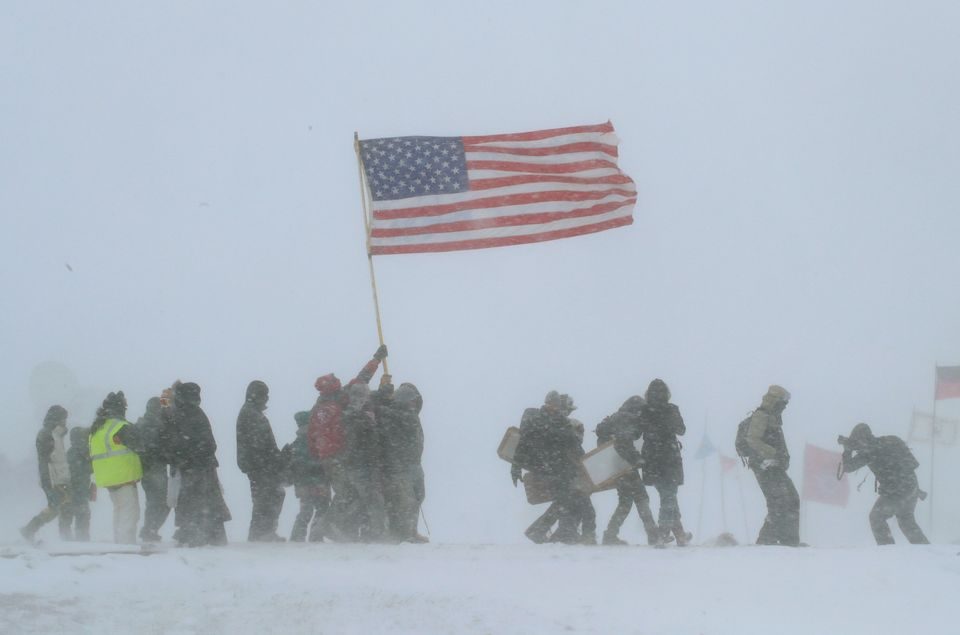 "CANNON BALL, ND - DECEMBER 05: Despite blizzard conditions, military veterans march in support of the ""water protectors"" at O"