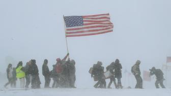 CANNON BALL, ND - DECEMBER 05: Despite blizzard conditions, military veterans march in support of the 'water protectors' at Oceti Sakowin Camp on the edge of the Standing Rock Sioux Reservation on December 5, 2016 outside Cannon Ball, North Dakota. Over the weekend a large group of military veterans joined native Americans and activists from around the country who have been at the camp for several months trying to halt the construction of the Dakota Access Pipeline. Yesterday the US Army Corps of Engineers announced that it will not grant an easement for the pipeline to cross under a lake on the Sioux Tribes Standing Rock reservation. The proposed 1,172-mile-long pipeline would transport oil from the North Dakota Bakken region through South Dakota, Iowa and into Illinois.  (Photo by Scott Olson/Getty Images)