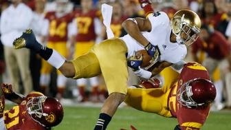 Notre Dame wide receiver TJ Jones (L) is brought down by USC's Lamar Dawson during their NCAA college football game at the Coliseum in Los Angeles, California November 24, 2012. REUTERS/Lucy Nicholson (UNITED STATES  - Tags: SPORT FOOTBALL)