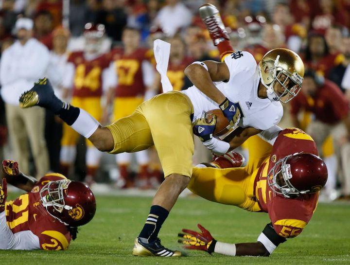 Notre Dame wide receiver T.J. Jones is brought down by USC's Lamar Dawson at the Coliseum in Los Angeles on Nov. 24, 2012. Da