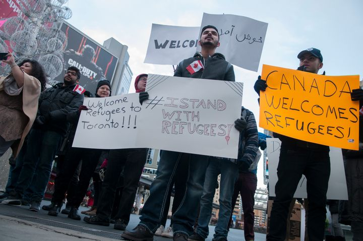 People take to the streets in Toronto on Nov. 22, 2015 with banners and signs rejecting Islamophobia and welcoming refug