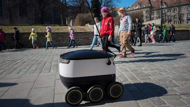 Schoolchildren watch as a self-driving delivery robot developed by Starship Technologies drives past them in Tallinn, Estonia