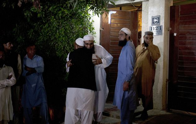 Relatives and friends of Pakistani singer-turned Islamic preacher Junaid Jamshed, comfort each other...