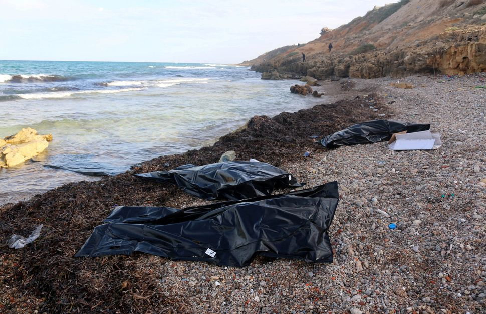 The dead bodies of migrants that washed ashore are seen in body bags at a beach in the coastal town of Tajoura, east of Tripo