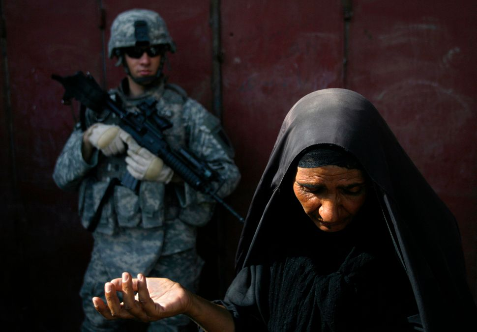 An Iraqi woman tries to explain to American soldiers that she had nothing to do with illegal fuel sellers in Baghdad on Aug.