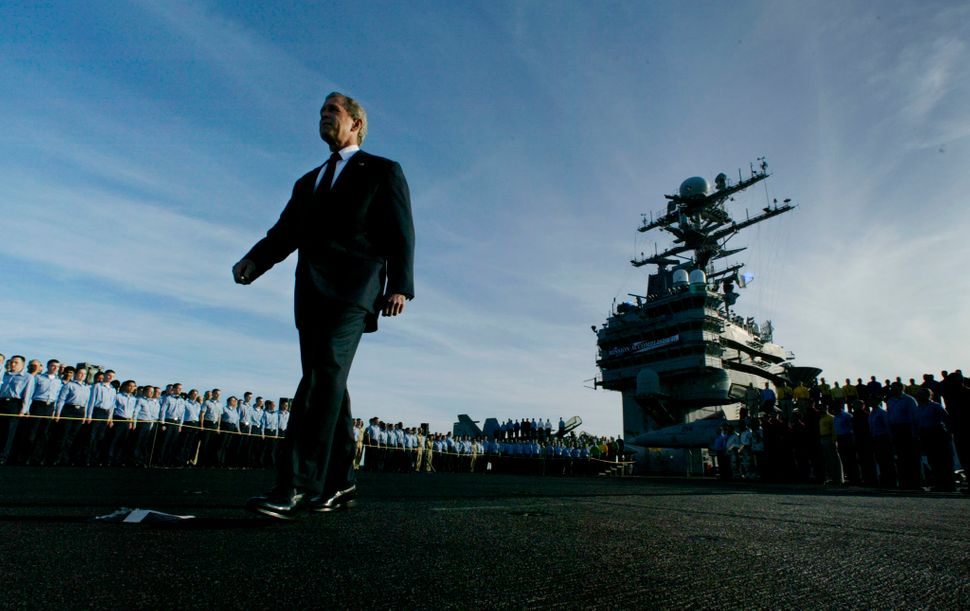 """Bush passes crew members as he walks the deck of the aircraft carrier USS Abraham Lincoln, on May 1, 2003, just before his """"m"""