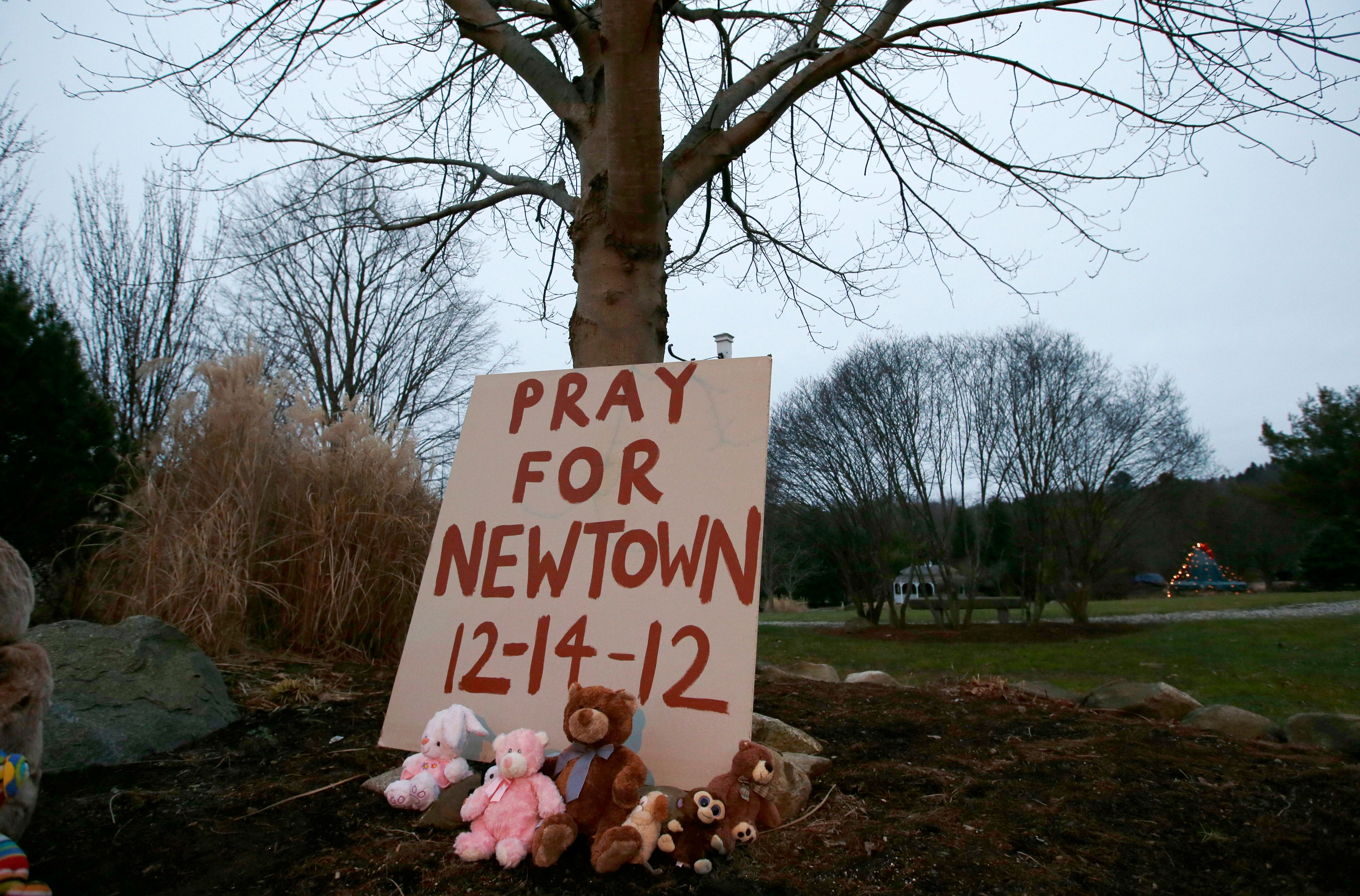 A sign stands at a makeshift memorial in Newtown, Connecticut early Sunday December 16, 2012. Twelve girls, eight boys and six adult women were killed in the shooting on Friday at the Sandy Hook Elementary School in Newtown.  REUTERS/Mike Segar   (UNITED STATES - Tags: CRIME LAW EDUCATION TPX IMAGES OF THE DAY)