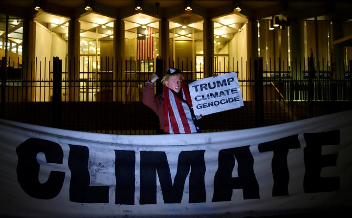 A man wearing a Trump mask protests during a demonstration against climate change outside the U.S. Embassy in London in