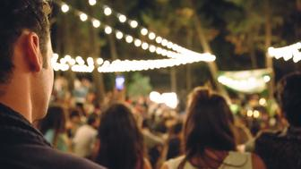 Back view of young man sitting and enjoying in a open night music festival outdoors on summer