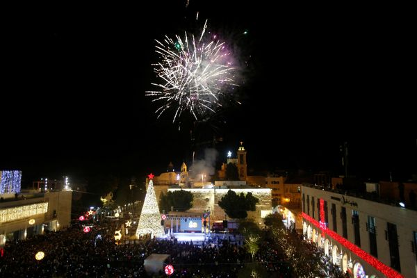 Fireworks explode during a Christmas tree lighting ceremony outside the Church of the Nativity in the West Bank town of Bethl