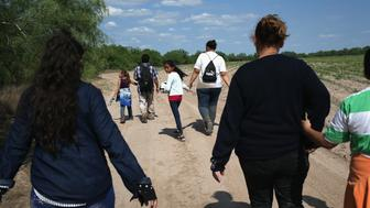 ROMA, TX - APRIL 14:  Central American immigrant families walk through the countryside after crossing from Mexico into the United States to seek asylum on April 14, 2016 in Roma, Texas. Border security and immigration, both legal and otherwise, continue to be contentious national issues in the 2016 Presidential campaign.  (Photo by John Moore/Getty Images)