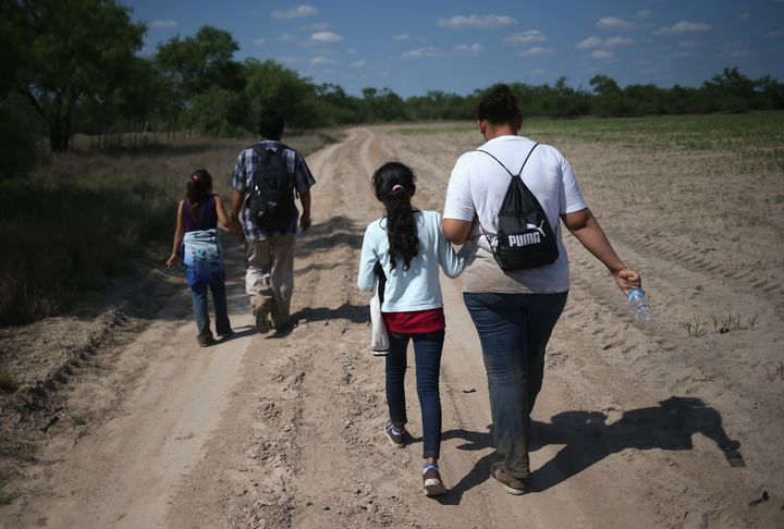 Central American immigrant families walk through the countryside in Roma, Texas, in April after crossing from Mexico into the