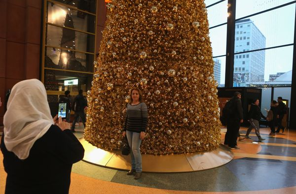 A shopper photographs another with a mobile phone in front of a Christmas tree in a shopping mall on November 30, 2016 in Ber