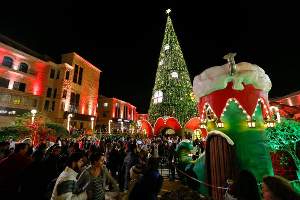 People gather around an illuminated Christmas tree in Byblos city in northern Lebanon November 24, 2016.