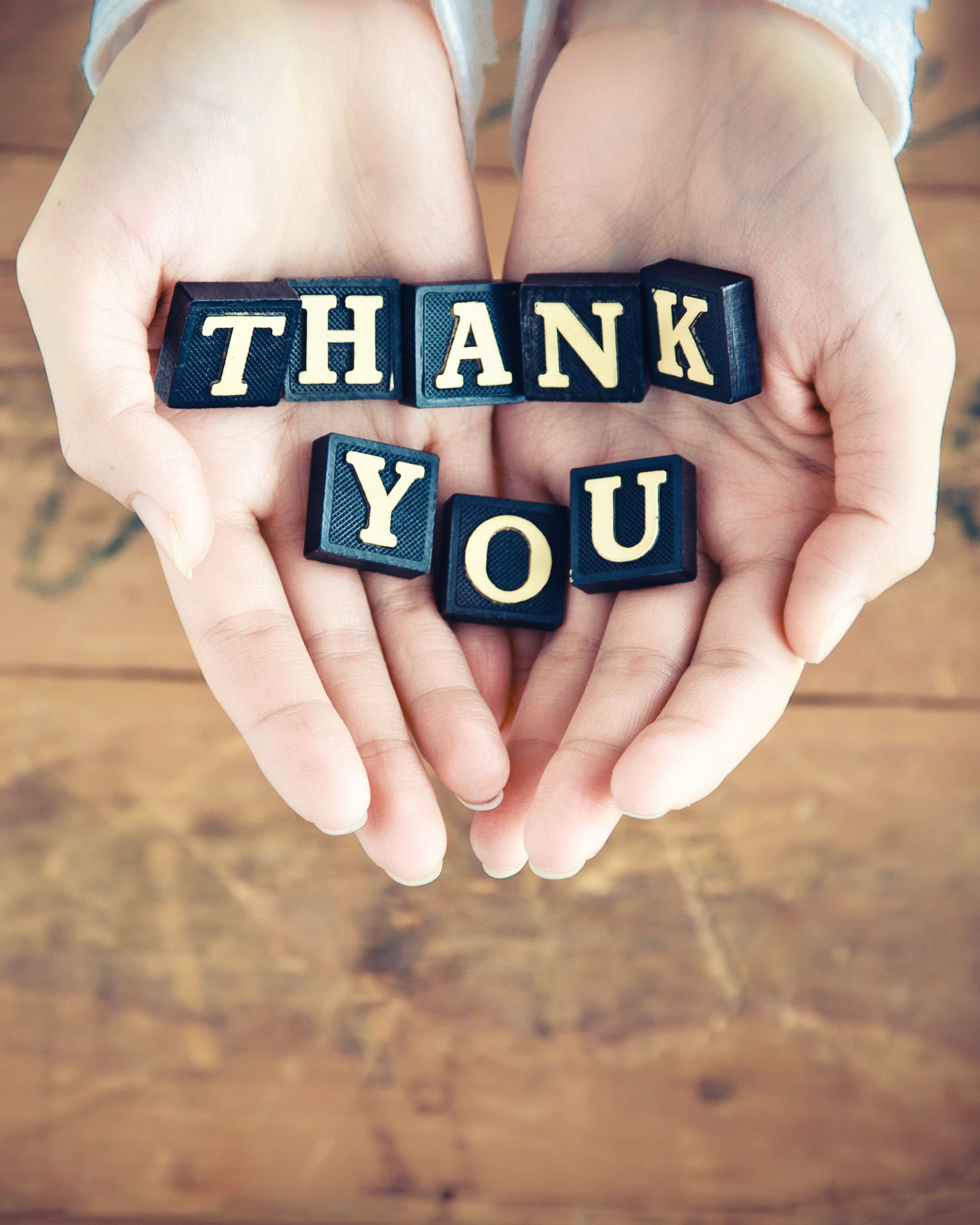 Thank you written in cupped hands.