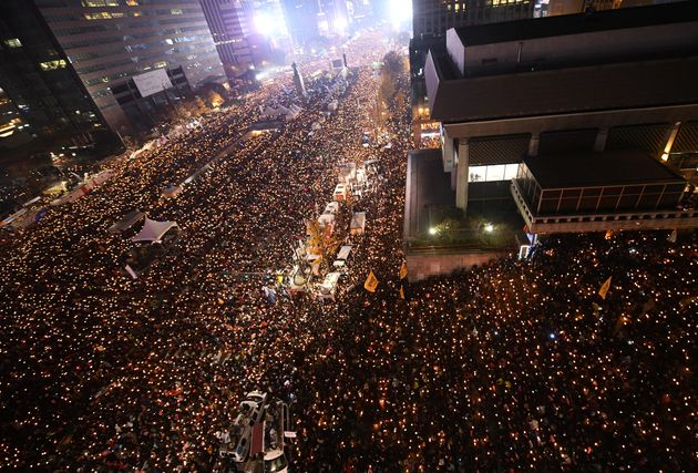 Protesters hold candles during an anti-government rally in central Seoul on Nov. 19, 2016, aimed at forcing...