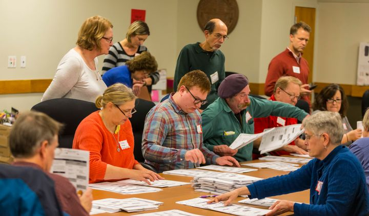 Designated observers watch tabulators recount presidential ballots in Madison, Wis., on Dec. 1, 2016.