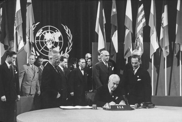 The United States officially Signs the UN Charter.  President Harry S. Truman looks on from left.