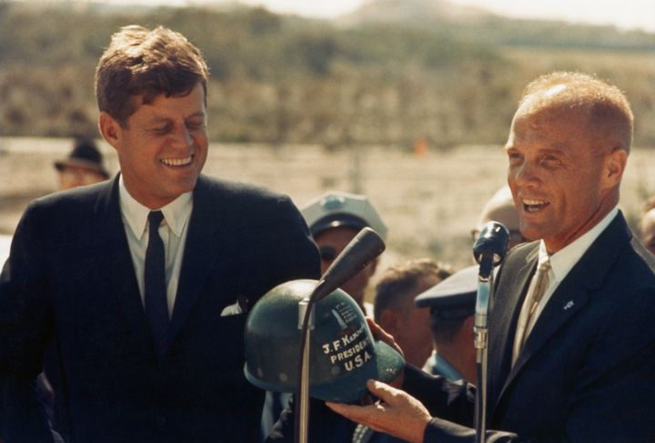 Astronaut John Glenn hands a hard hat to President John F. Kennedy at Cape Canaveral in Florida. Several days before, Glenn b