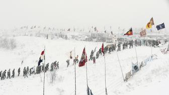 """Veterans join activists in a march to Backwater Bridge just outside the Oceti Sakowin camp during a snow fall as """"water protectors"""" continue to demonstrate against plans to pass the Dakota Access pipeline adjacent to the Standing Rock Indian Reservation, near Cannon Ball, North Dakota, U.S., December 5, 2016.  REUTERS/Lucas Jackson"""
