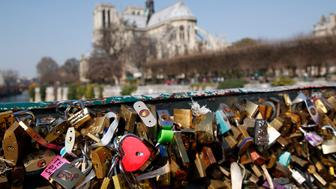 Love padlocks on the Pont de l'archeveche near Notre-Dame cathedral on March 23, 2015 in Paris, France. The accumulation of 'love locks', a popular phenomenon in many European cities, where couples attach a lock to symbolize their love for mesh panels on the sides of the bridge begins to pose safety problems, because of their mass weight. Photo by Justin Lorget (Photo by chesnot/Corbis via Getty Images)