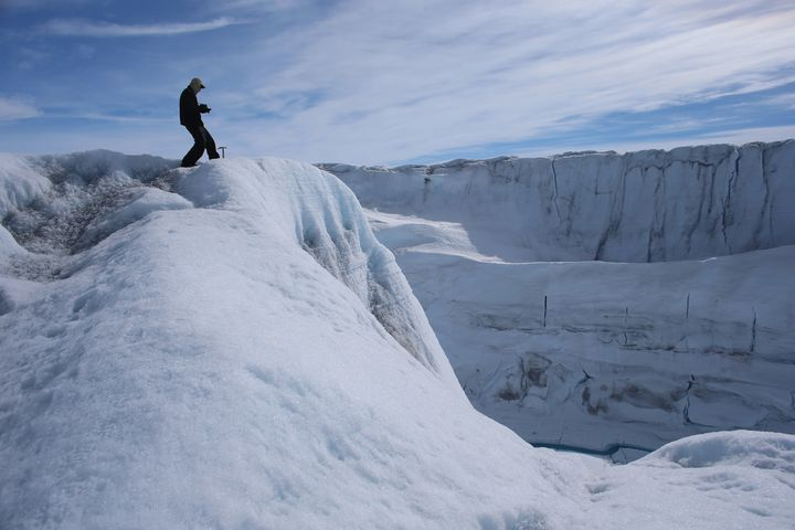 A researcher observes a canyon created over time by a meltwater stream on the Greenland's ice sheet, July 16, 2013.
